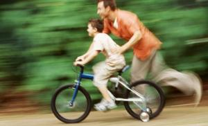 Dad and son on bike with training wheels